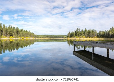 old wooden dock looking out over a motionless Lillian Lake with a mirror like reflection in the morning in British Columbia, Canada