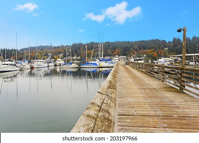 Old wooden dock with water view and boats. Gig Harbor.
