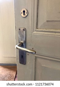 Old wooden door in ajar painted in green tones with handle and lock in silvery toned metal.