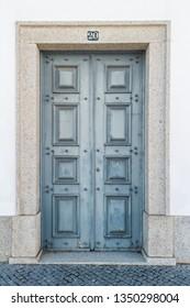 The old wooden door. Ancient antique wooden in an old wall. Ancient decorative wooden door. Historical art style facade of an elite expensive antique door.