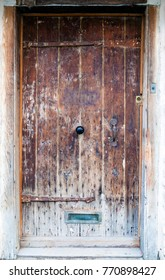 Old wooden door, An ancient oak wood door with ornate metal handle, hinges, old door bell, and spy hole.