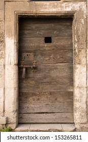 old wooden door of ancient prison in Arles, France