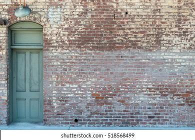 Old Wooden Door In A Brick Wall