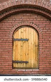 Old wooden door in brick wall in monastery