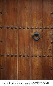 Old wooden door with circular metal handle