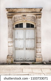 An old wooden door with a classic stone frame anchors an entry into an otherwise non-descript house in the Chablis region of France.