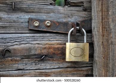 Old wooden door closed with metal key locker.