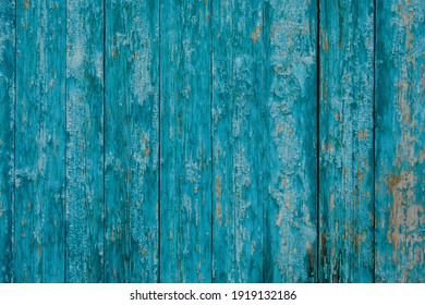 old wooden door covered with old cracked turquoise color paint