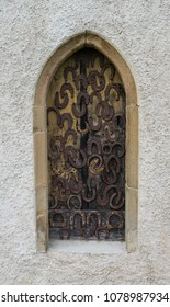 Old wooden door covered with rusty horseshoes