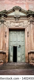 Old wooden door entrance to the Church.  Italian renaissance door frame. Antique building architectural detail. Embelished entrance with flourish motif.