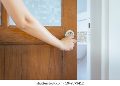 Old wooden door and hand open with handle and blur toilet  blackground