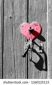 Old wooden door with heart shape lock keyhole and handle. Retro toned black white red photo. Open you heart concept. Love, mercy, charity idea. Vintage background.