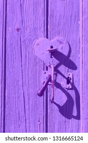Old wooden door with heart shape lock keyhole and handle. Retro toned violet photo. Open you heart concept. Love, mercy, charity idea. Vintage background.