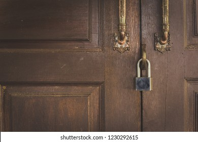 Old wooden door with lock for key with silver.