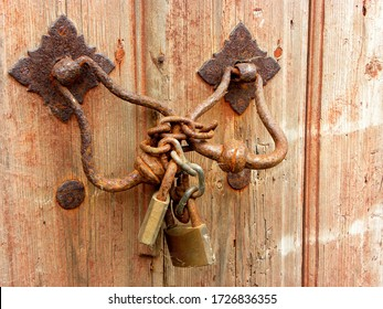 Old wooden door locked by a padlock and a rusty chain.