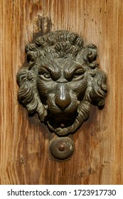 An old wooden door with a metal handle shaped like a lion's head.