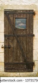 Old wooden door with metal hinges and lock
