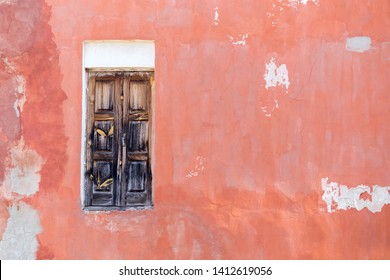 old wooden door to nowhere, against the background of the old pink wall with scratches
