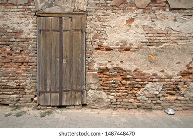 Old wooden door on the ruined wall of an abandoned house.