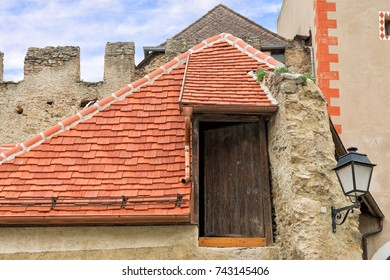Old wooden door on top of a house in Durnstein. Austria. The roof has been renovated with new red cedar shingles. In the background, we can see part of the old city walls.