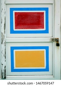 An old wooden door with red amd yellow painted rectangles
