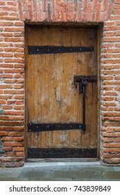 old wooden door in a rustic style, rusty padlock.