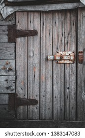 Old wooden door and rusty deadbolt in a small barn