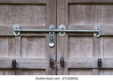 An old wooden door with rusty old locks and newer silver locks