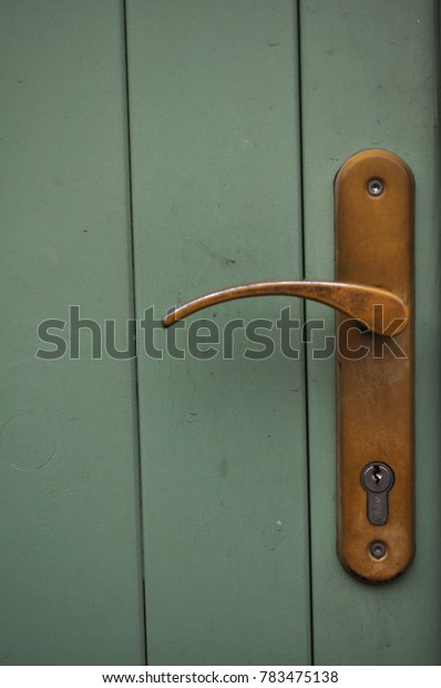 old wooden door with scratched lacquer , old plastic / metal iron handle covered in dust
