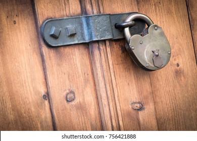 Old wooden door with steel heavy padlock hanging on a door latch