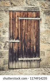 Old wooden door in stone ancient wall. Toned