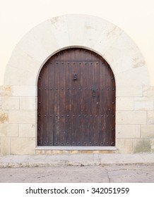 Old wooden door with stone arch