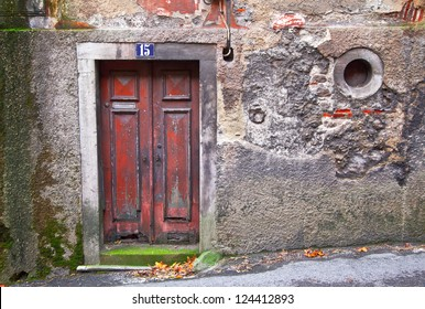 Old wooden door in a stone wall with a round window. Sintra. Portugal.