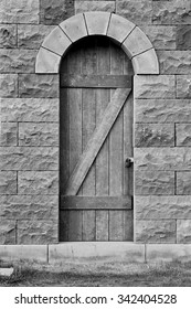 Old wooden door in a stone wall in black and white