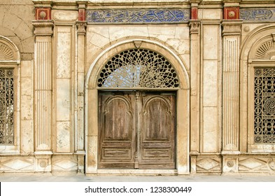Old wooden door and vintage wall with two old windows located in Saladin's castle with some blue text above and red ornament above columns