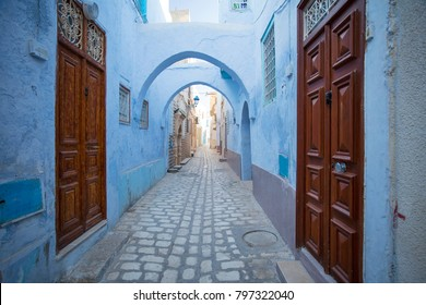 old wooden doors and blue walls on the street in old town in Tunisia