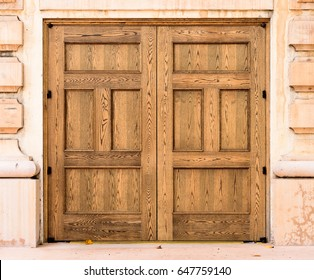 Old wooden doors on old building in public park with out door knob or handle. Doors appear to be oak with two vertical panels and two horizontal panels.