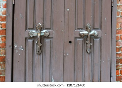 Old wooden doors with orthodox crosses at the entrance to the chapel as background.