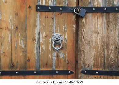Old wooden doors with a relief of a head of the lion and the lock
