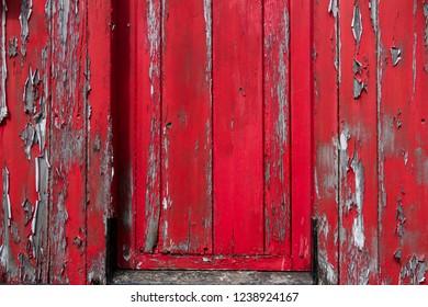Old wooden door/wall with peeling red paint