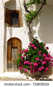 Old wooden doorway arch in Kritsa village, Crete, Greece with blooming flower vine