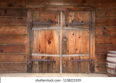 Old wooden double doors with rusty weathered hardware, wooden barrels stacked beside door. Close up.