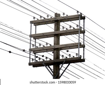 an old wooden electric utility power pole with a mess of wires isolated on white