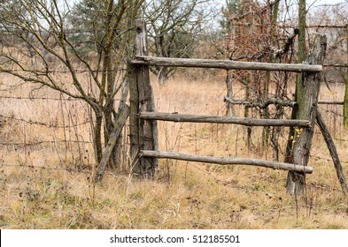 Old wooden fence with barbed wire in rural area