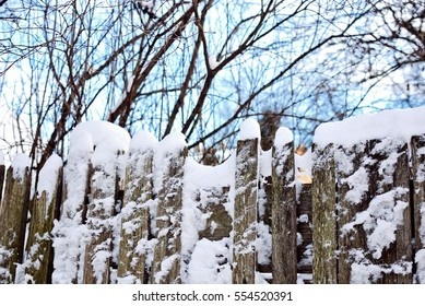 Old wooden fence covered with snow