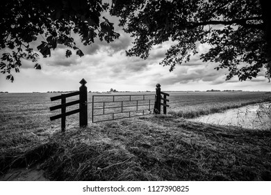 Old wooden fence for the entrance of a flat and green grassland. A look at the polder of the Kamper eiland near Kampen