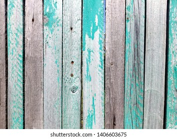 Old wooden fence with faded color. Worn old paint on the fence. Russian vintage. Beautiful old boards. Decor for design style shabby chic. Barn boards for interior design. Sunny weather.