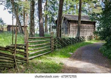 Old wooden fence and a road to a farmhouse