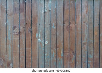 Old wooden fence texture with some dirty blue paint, knots and scratches. Retro background - aged lumber surface.