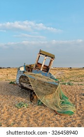 An old wooden fishing boat on a shingle beach at Dungeness on the Kent coast